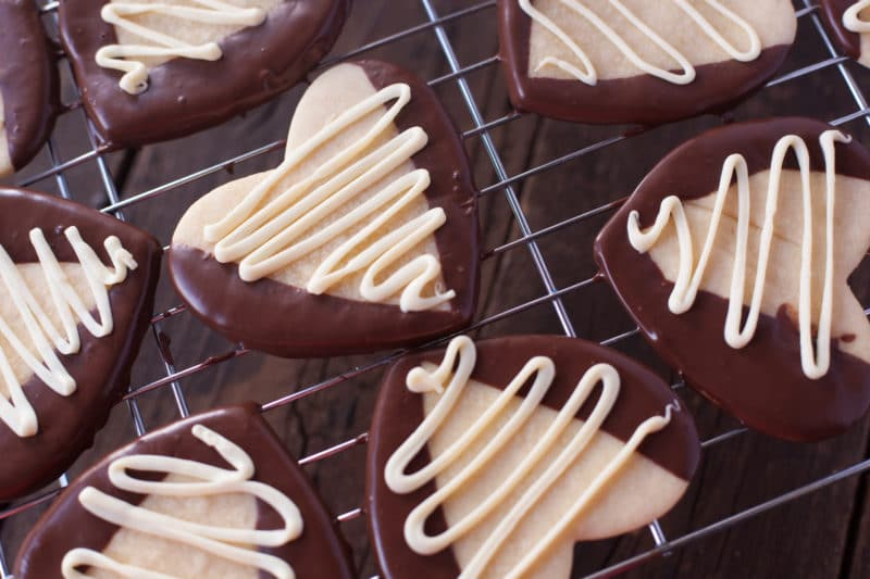 Heart shaped Valentine's Day Sugar Cookies dipped in chocolate and drizzled with white chocolate sitting on a cooling rack over a dark cookie sheet