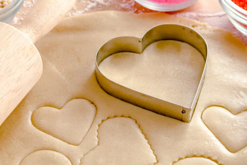 Cutting out heart shaped Valentine's Day Sugar Cookies