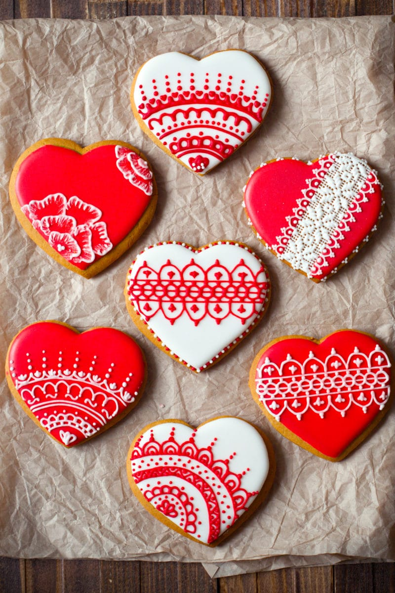 Heart cookies with intricate lace designs in red and white icing on brown wooden background