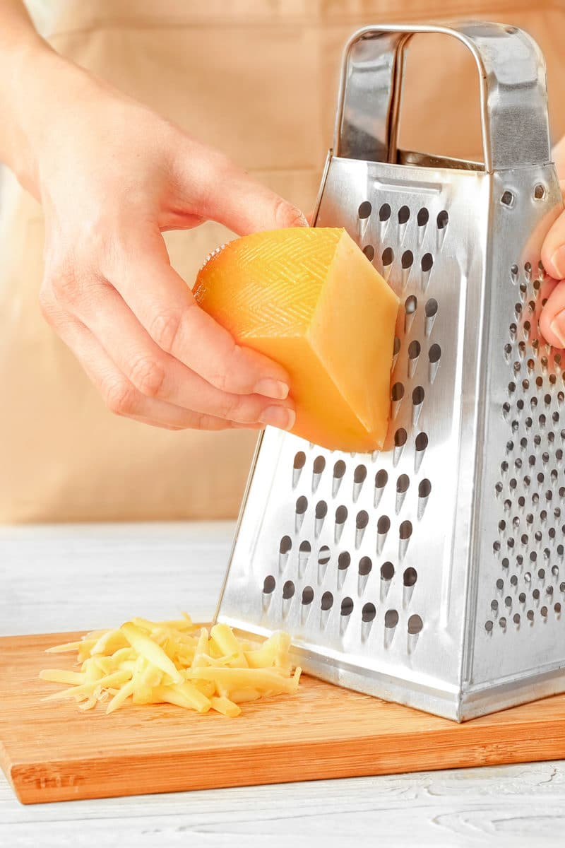 hands shredding orange cheese on a silver grater