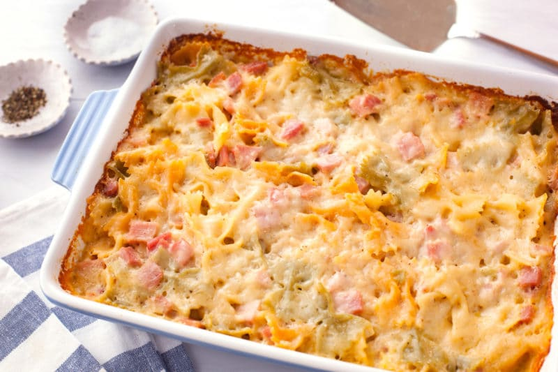 Blue and white casserole dish with golden cheesy pasta ham bake