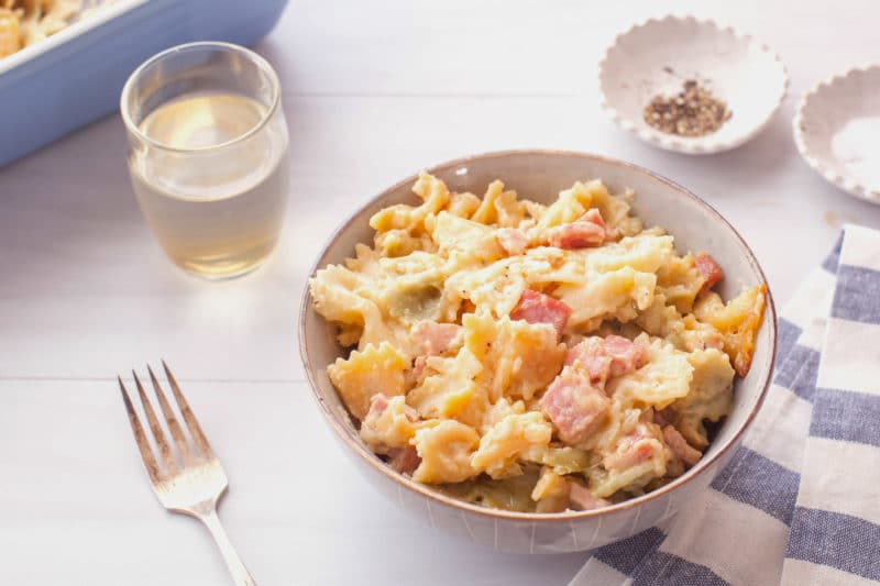 Dinner of ham pasta bake in a bowl with a glass of white wine