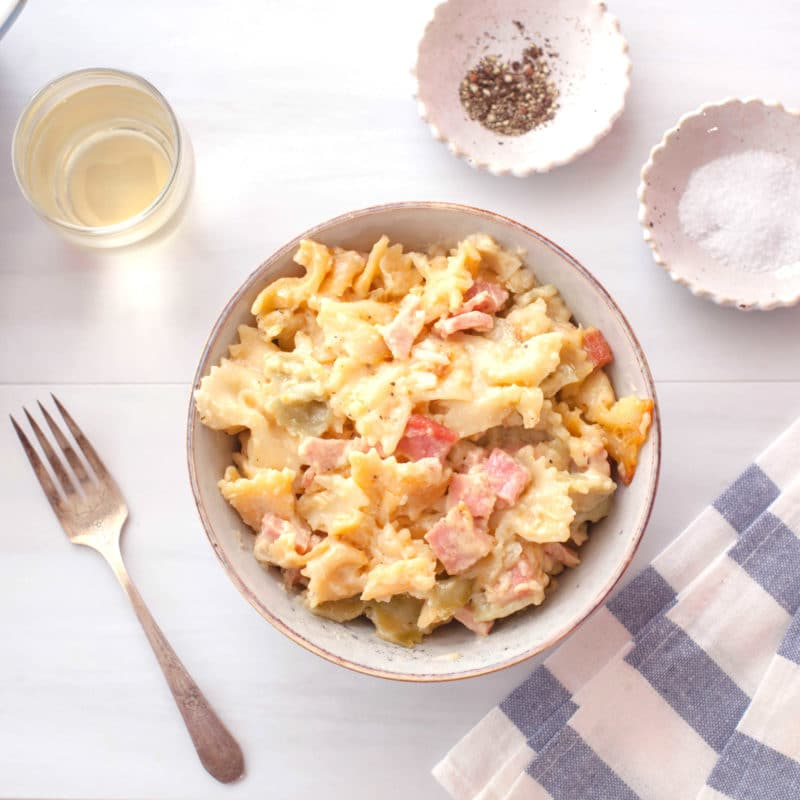 Bowtie pasta and ham in a creamy cheese sauce in a grey bowl with a blue and white striped napkin and glass of white wine