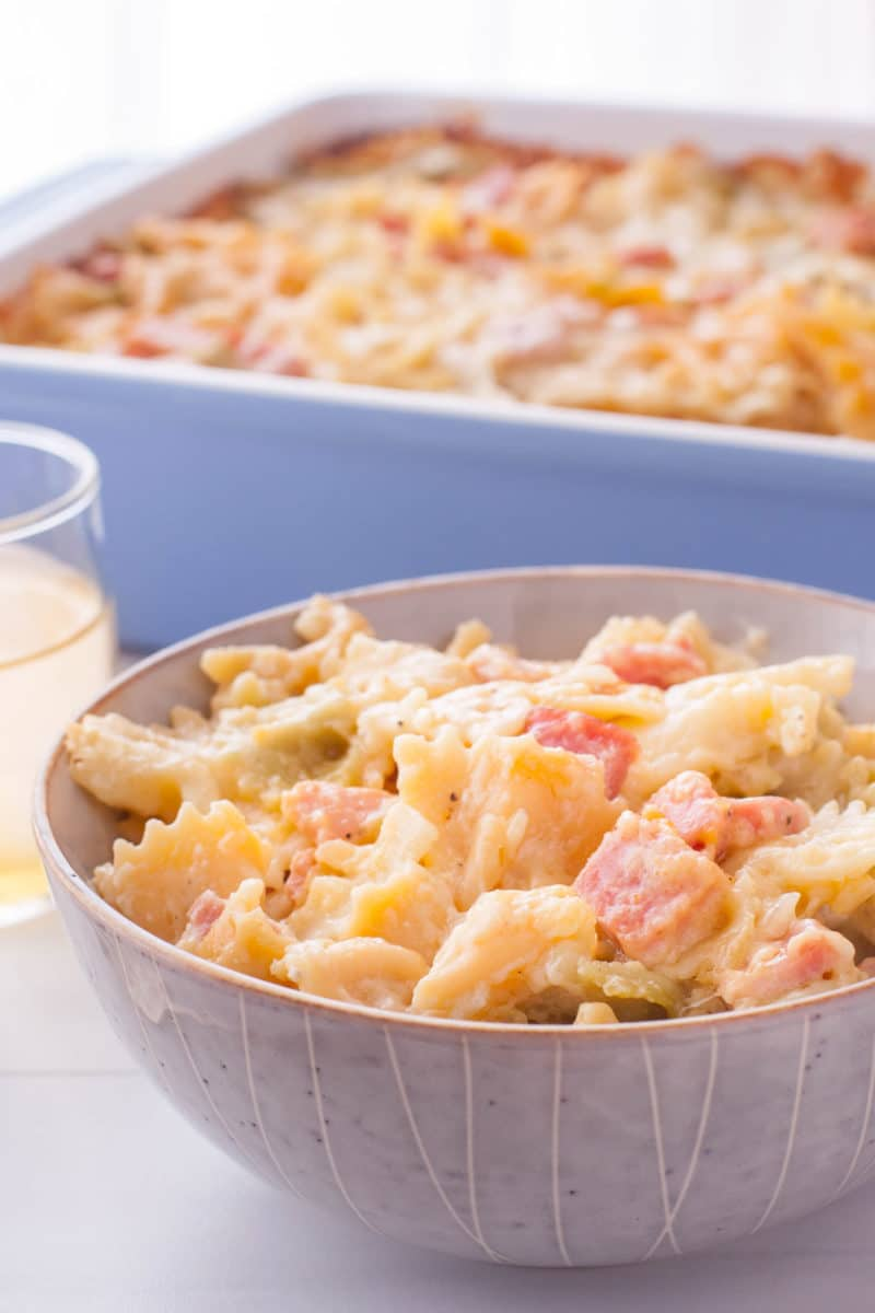 bowl of cheesy bowtie pasta and ham with the casserole in the background