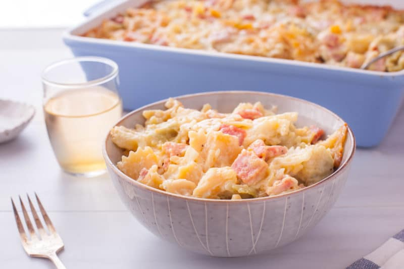cheesy pasta bake serving in a gray bowl with full casserole in a blue dish in the background