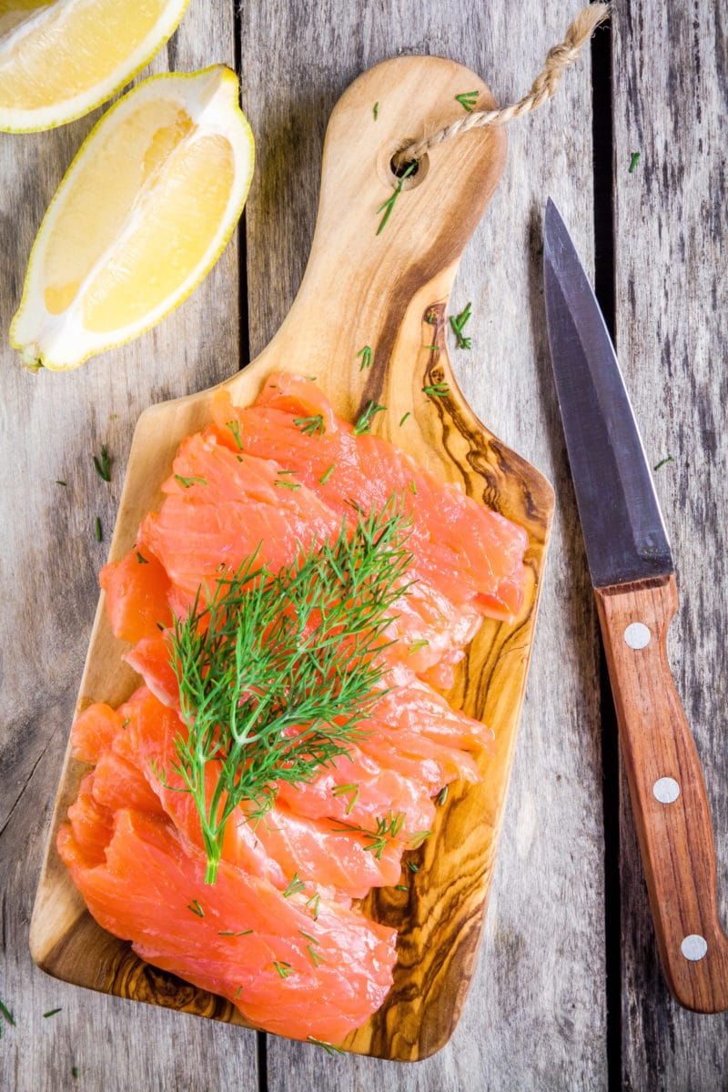 smoked salmon on a small cutting board with fresh dill and lemon wedges