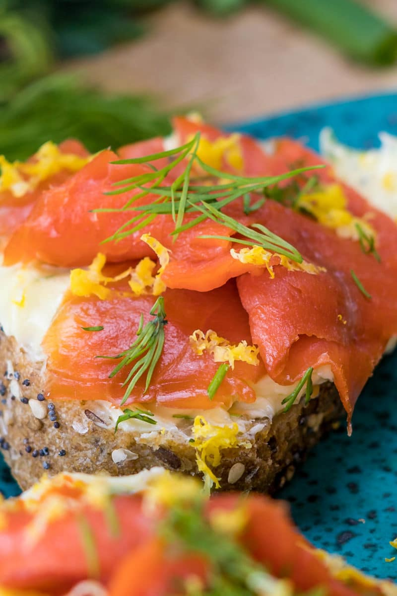 close up of thin sliced smoked salmon on lemon herb buttered bread topped with lemon zest and chopped dill