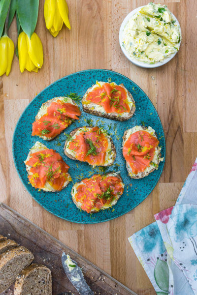 Smoked salmon breakfast toasts on blue plate with yellow tulips and sliced bread nearby